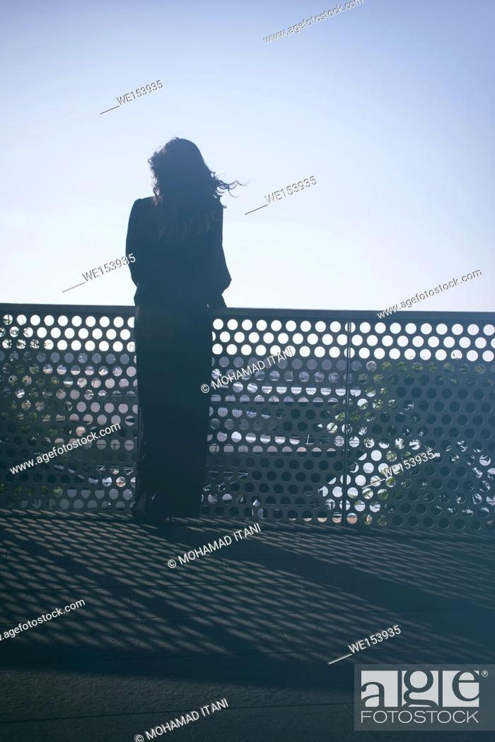 Stock Photo: Rear view silhouette of a young woman standing outdoors.