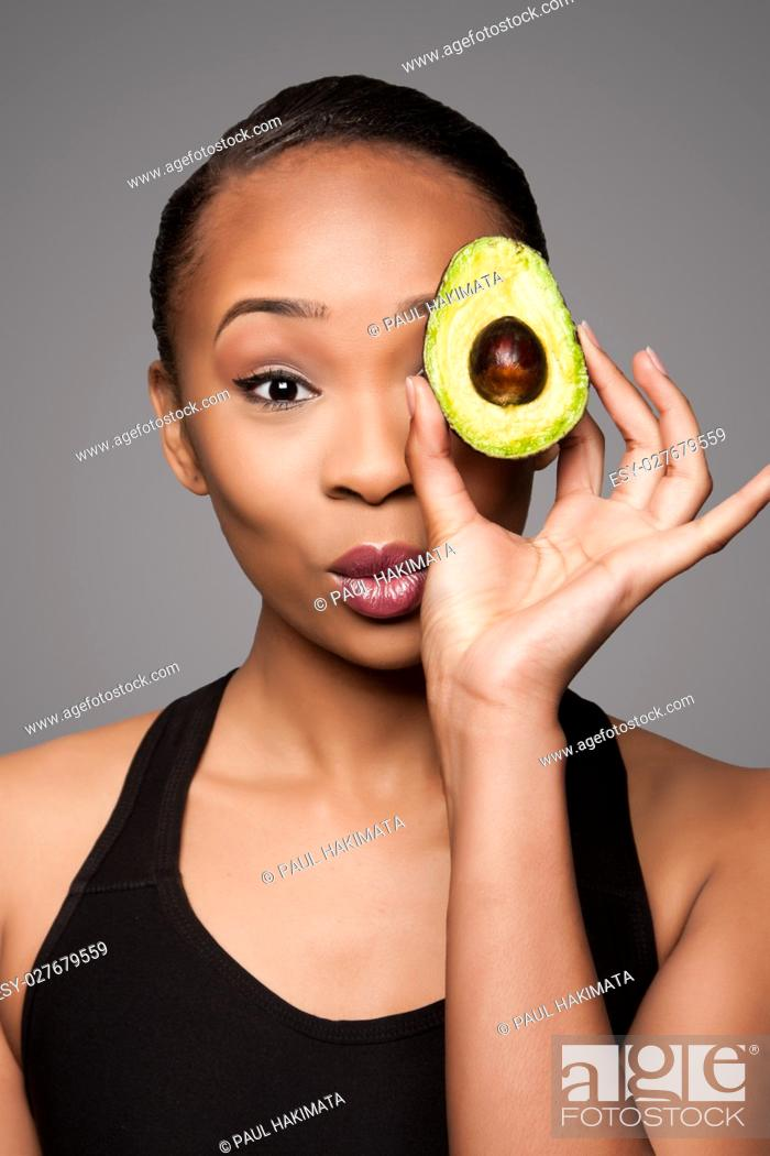 Stock Photo: Beautiful healthy happy black asian woman holding delicious avocado super fruit in front of eye.