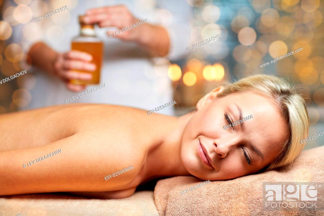 Stock Photo: people, beauty, spa, healthy lifestyle and relaxation concept - close up of beautiful young woman lying with closed eyes on massage table and therapist holding.