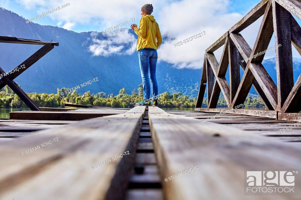 Photo de stock: Chile, Chaiten, Lago Rosselot, woman standing on jetty holding mug.