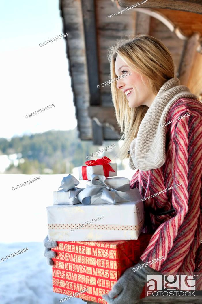 Stock Photo: Smiling woman holding Christmas gifts on cabin porch.