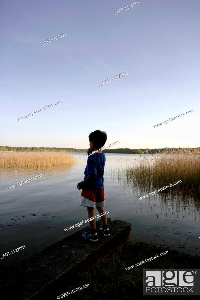 Stock Photo: Boy standing at edge of lake.