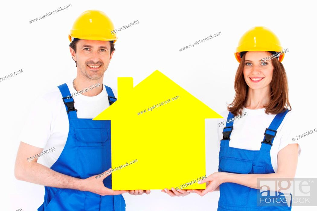 Stock Photo: Two happy smiling workers hold yellow house model outdoors at construction site.