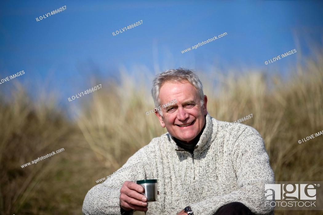 Stock Photo: A senior man sitting amongst the sand dunes, having a hot drink.