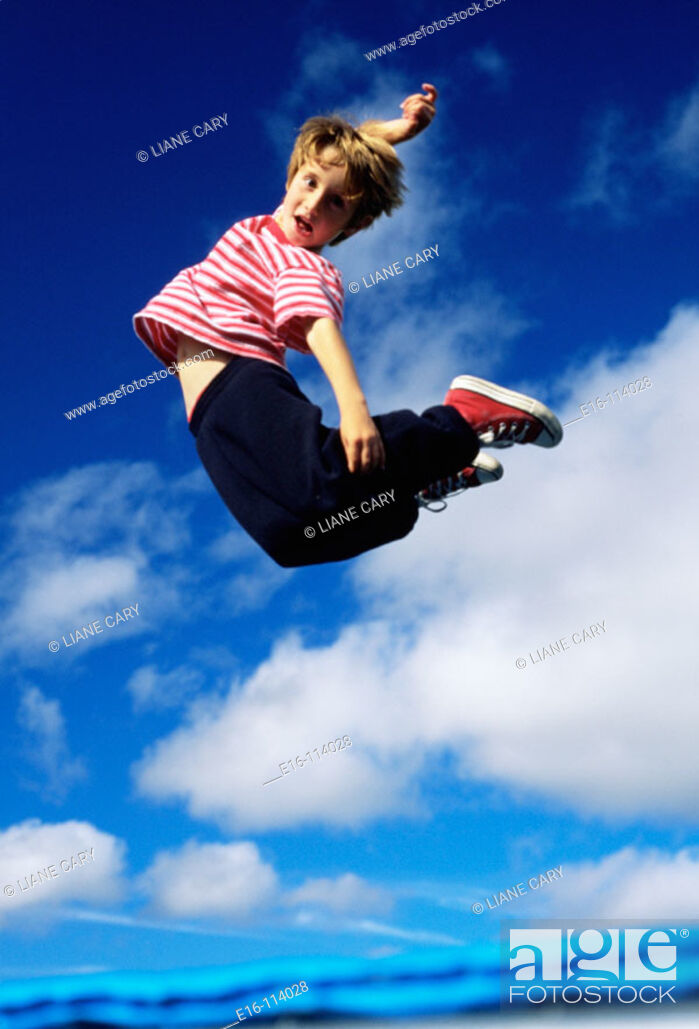 Stock Photo: Young boy jumping for joy on a trampoline.