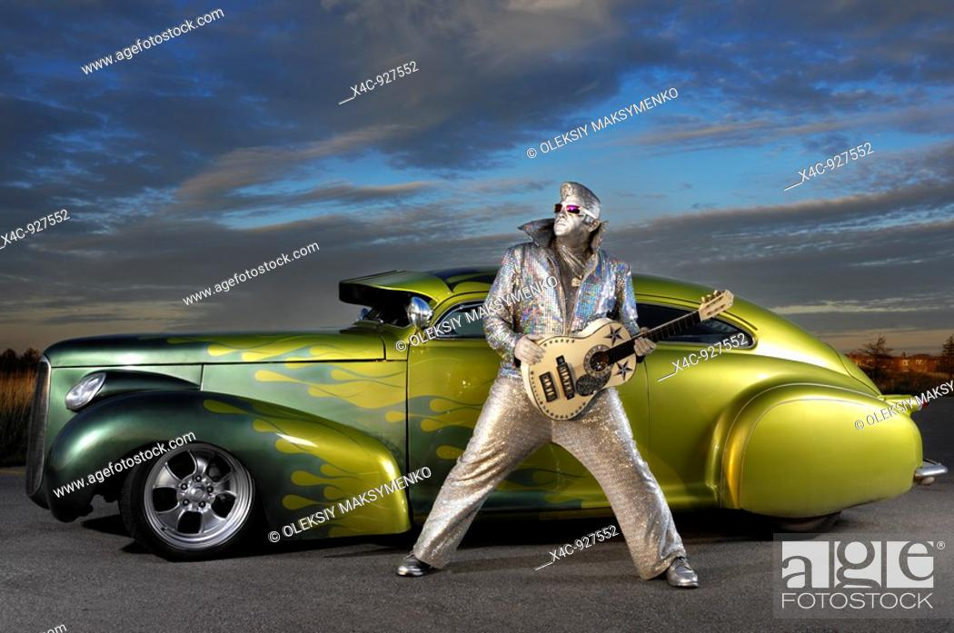 Stock Photo: Silver Elvis with a guitar standing in front of a custom lowride Studebaker hot rod under dramatic sunset sky  Performing artist Peter Jarvis from Toronto.