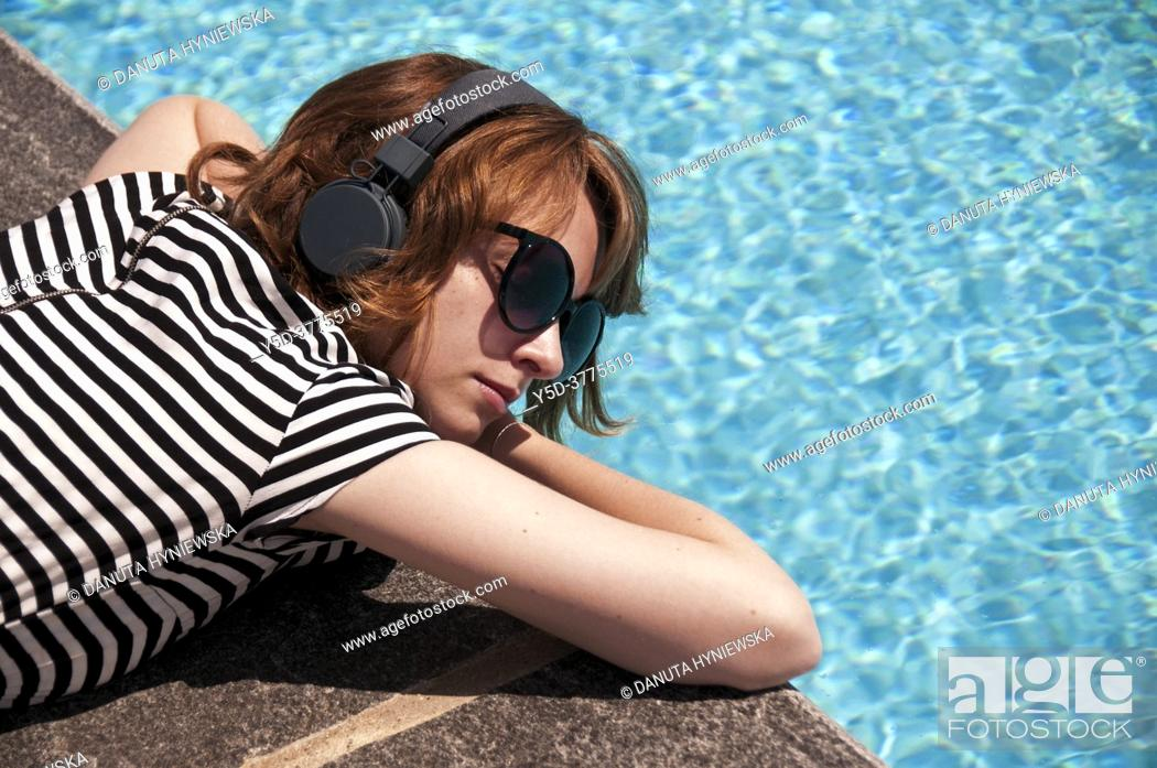 Stock Photo: Young female with headphones wearing sunglasses resting at poolside.
