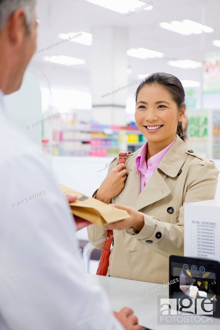 Stock Photo: Female customer smiling and making a purchase in pharmacy.