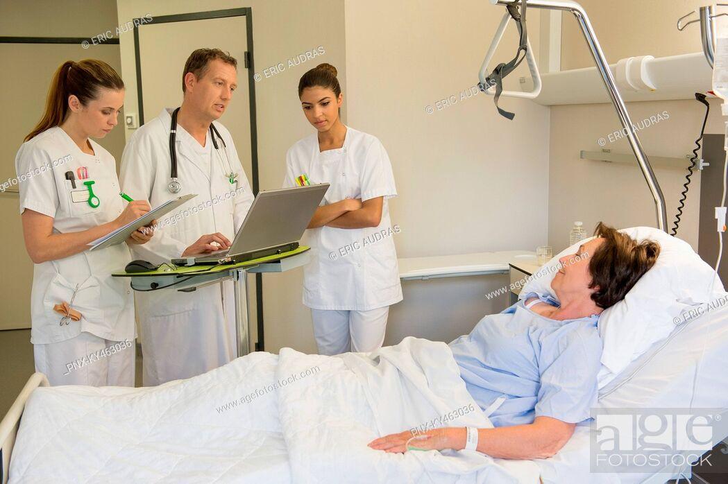 Imagen: Medical team attending female patient on hospital bed.