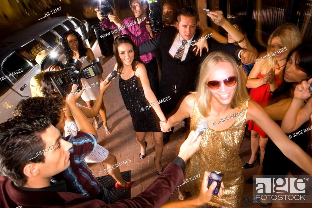 Stock Photo: Small group of young women and bodyguard surrounded by paparazzi, elevated view.