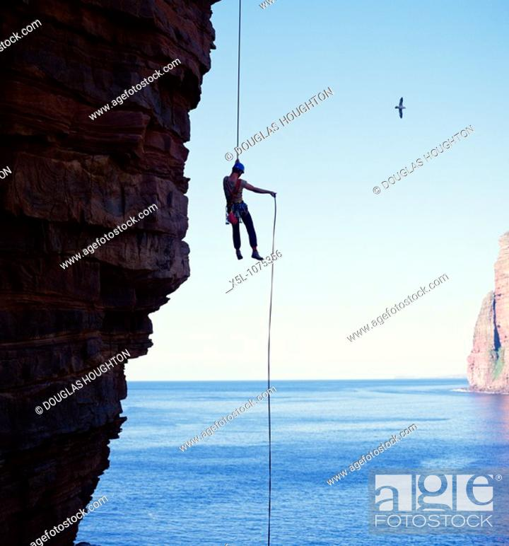 Stock Photo: ABSEILING SPORT Abseiler descending Old Man of Hoy seastack Orkney.