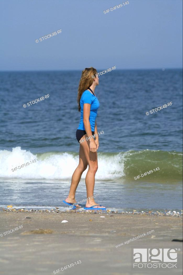 Stock Photo: Young woman promenading at the beach.