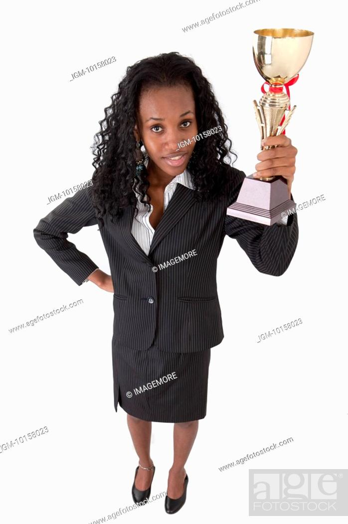 Stock Photo: Businesswoman holding a trophy and looking up.