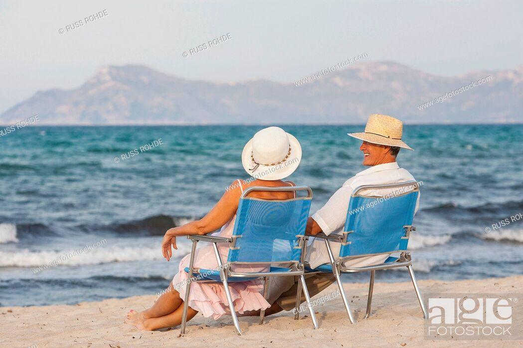 Stock Photo: Couple on deckchairs on beach, Palma de Mallorca, Spain.