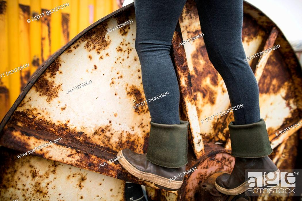 Stock Photo: Young adult standing on rusty equipment in a boat yard in Homer, Southcentral Alaska.