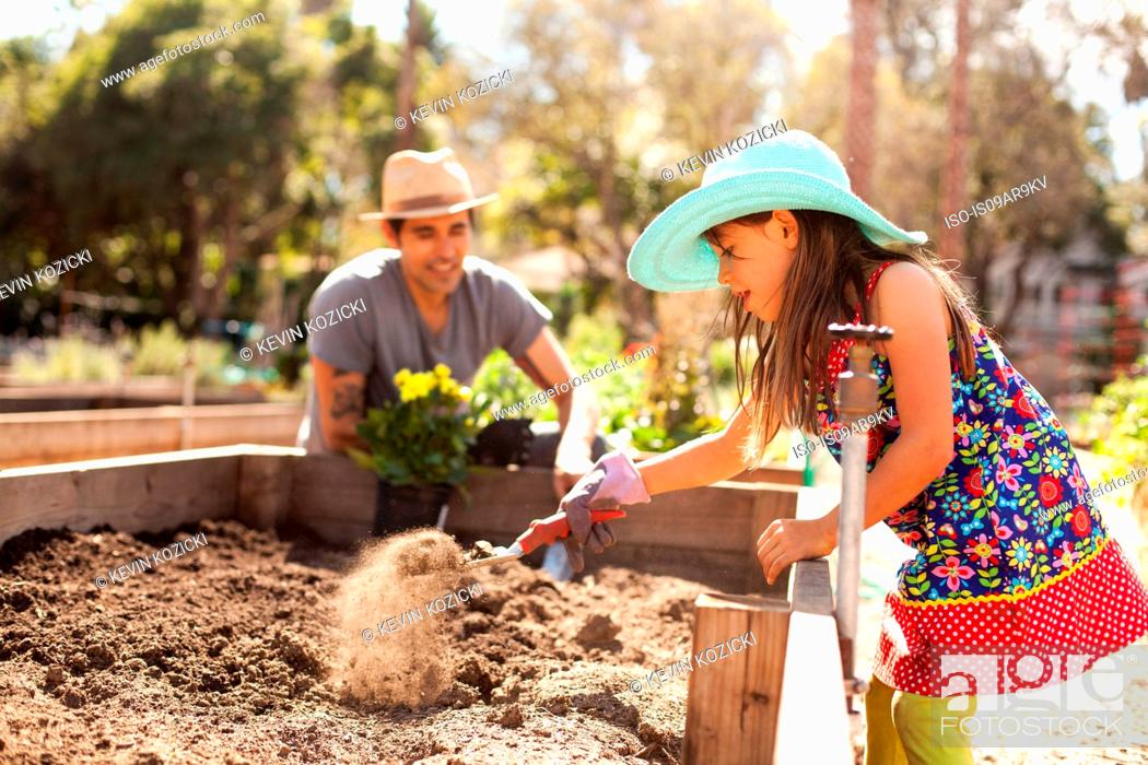 Stock Photo: Enthusiastic girl digging flower bed in community garden.