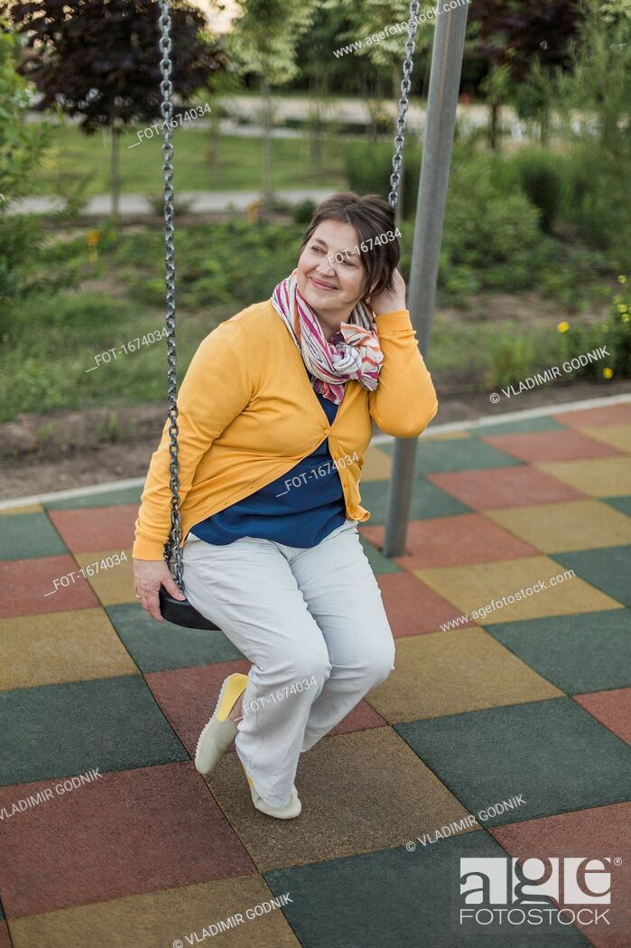 Stock Photo: Smiling woman looking away while sitting on swing at playground.