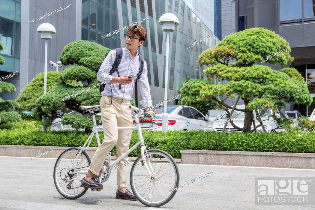 Stock Photo: Businessman with smartphone and bicycle.