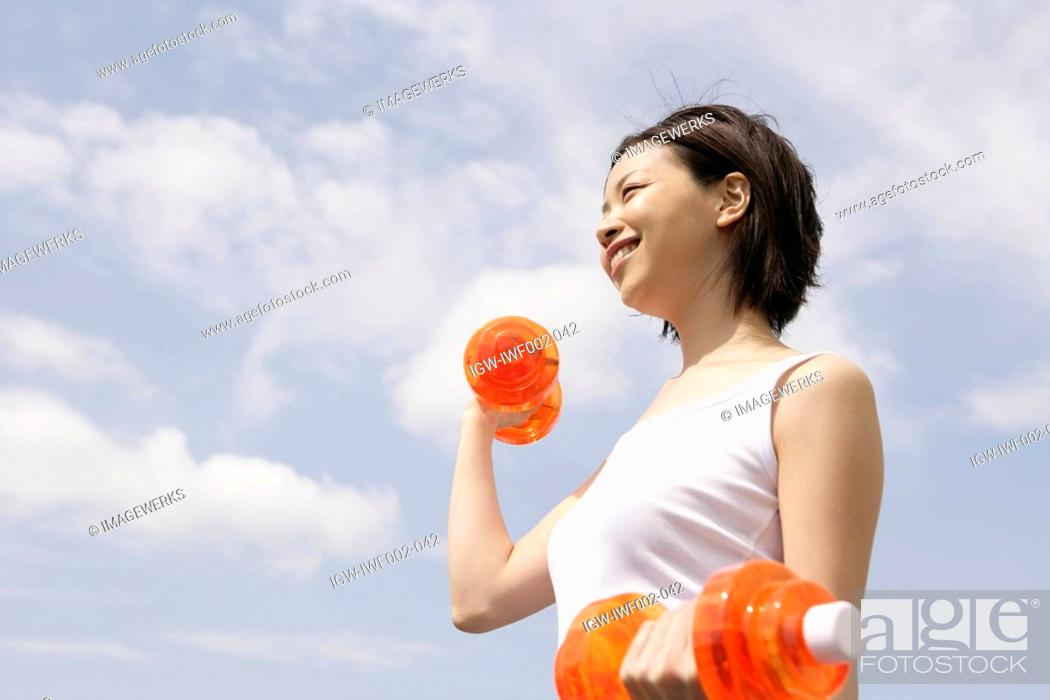Stock Photo: A woman exercising as she lifts the dumbbells.