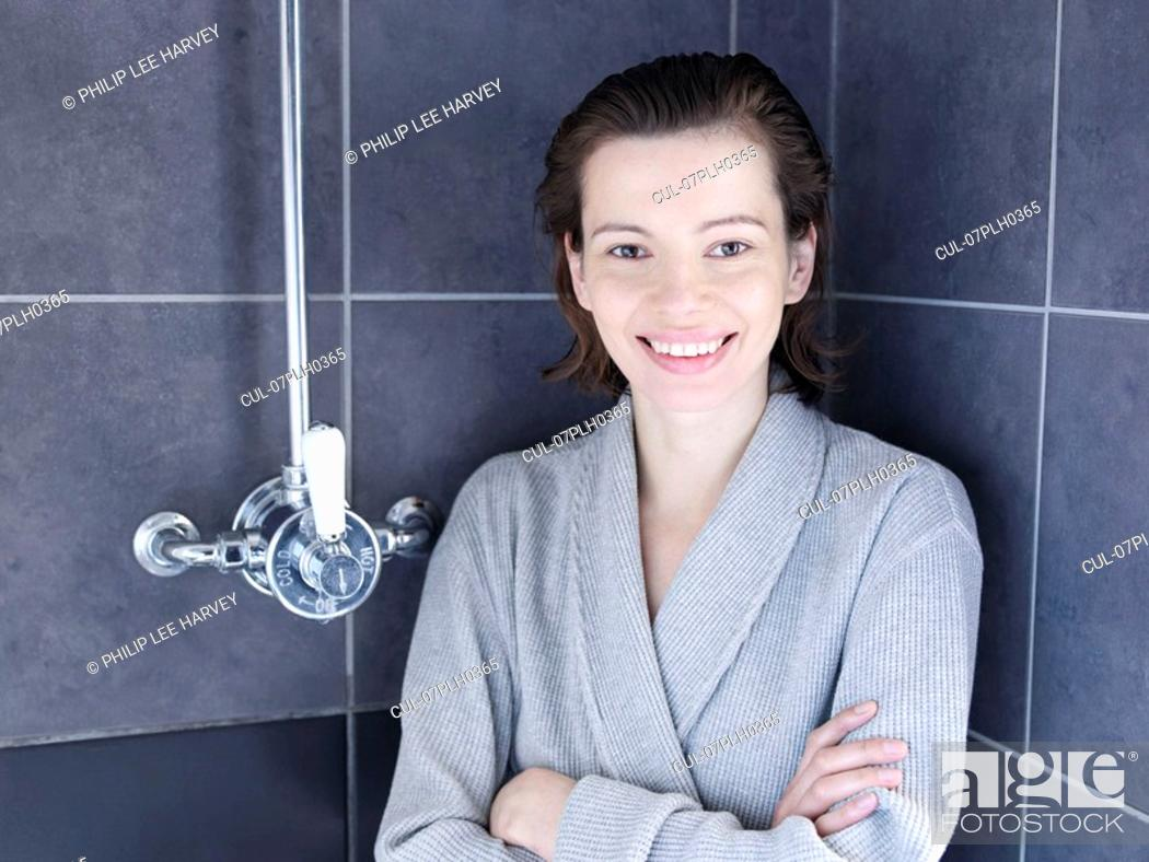 Stock Photo: Woman in bathrobe standing in shower.