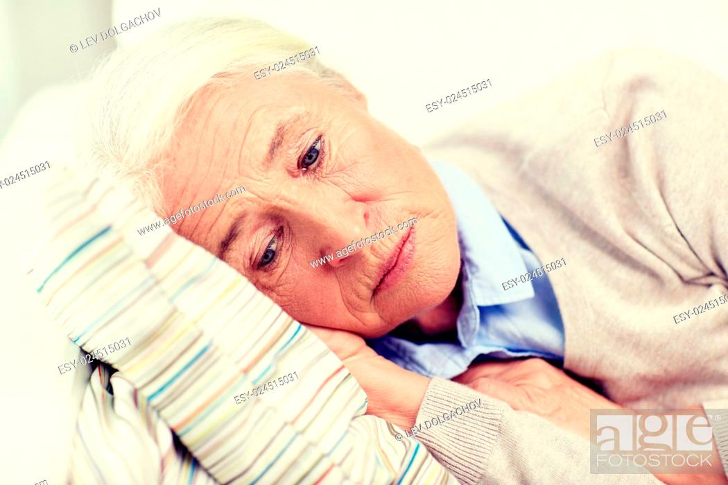Imagen: age, sadness, trouble, problem and people concept - sad senior woman sleeping on pillow at home.
