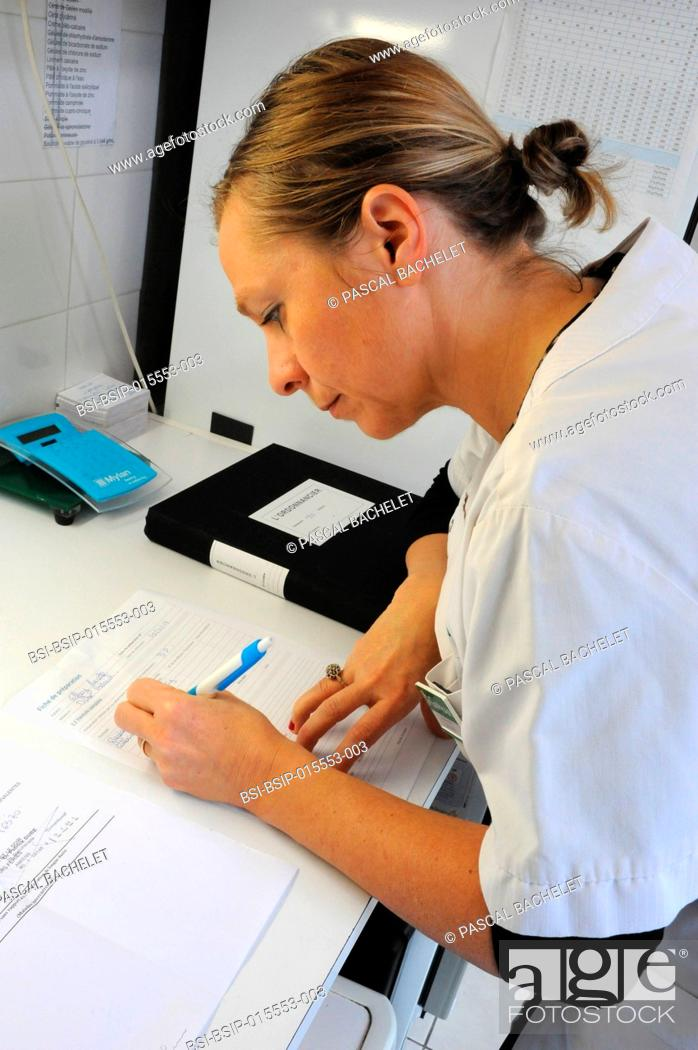 Stock Photo: Reportage in a pharmacy in Auxi-le-Château, France. A pharmacy technician prepares a glycerol starch-based treatment. Preparation sheet.