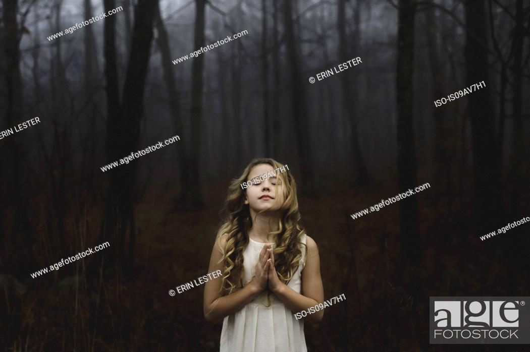 Photo de stock: Portrait of long blond haired girl with eyes closed and hands together in misty forest.