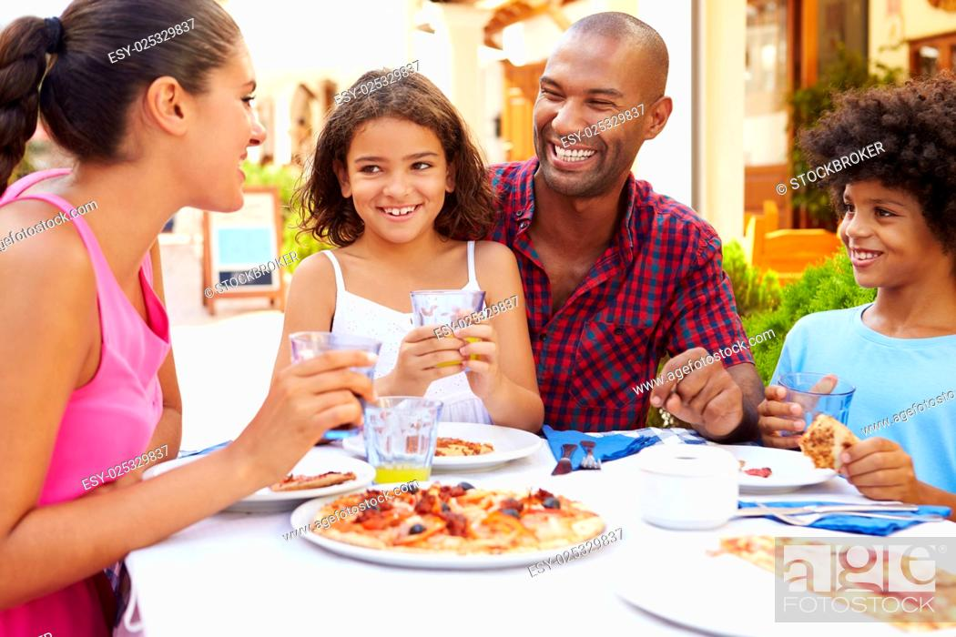Imagen: Family Eating Meal At Outdoor Restaurant Together.