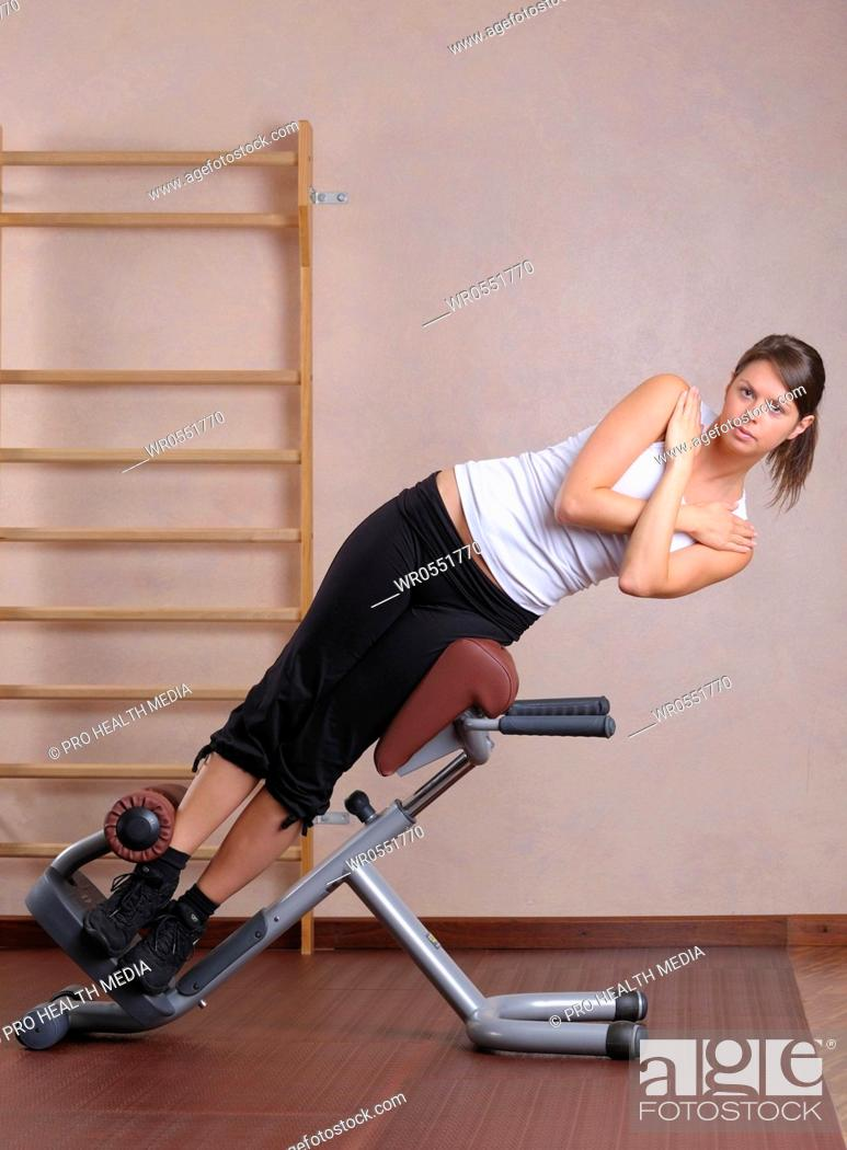Stock Photo: young woman training at a gym machine.