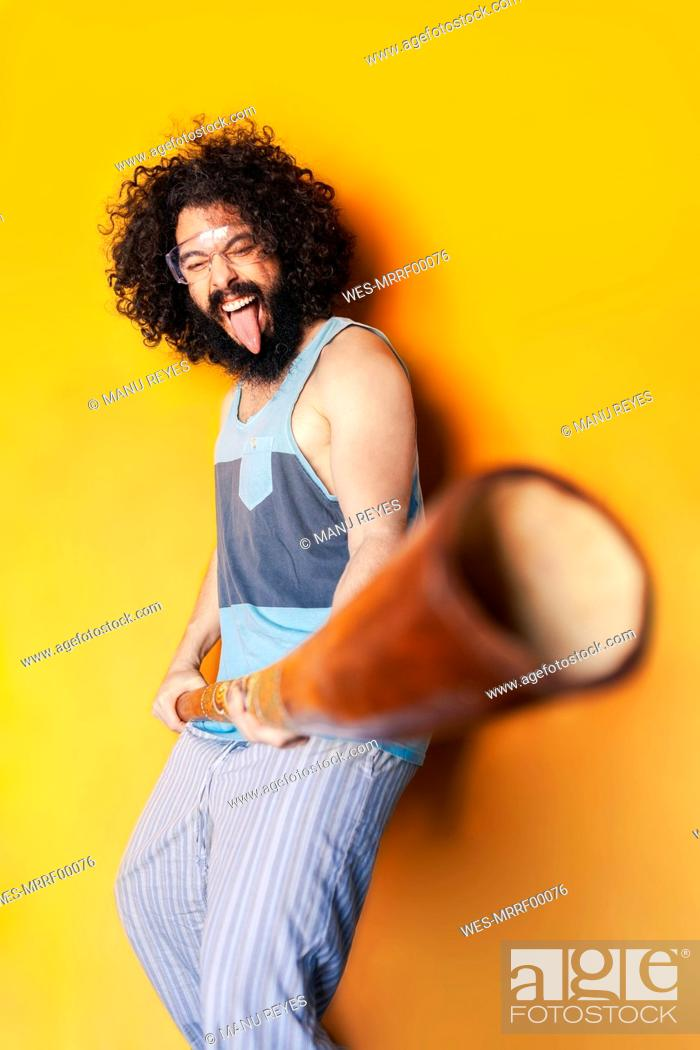 Imagen: Crazy man holding didgeridoo sticking out tongue while standing against yellow background.