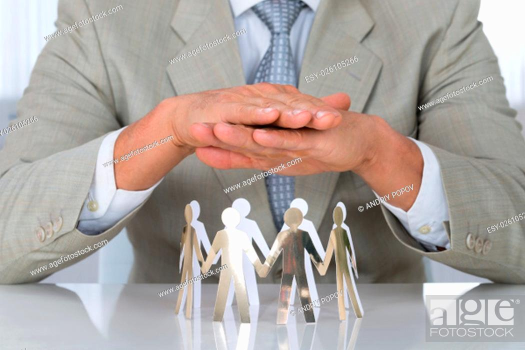 Stock Photo: Midsection of businessman protecting paper team on desk in office.