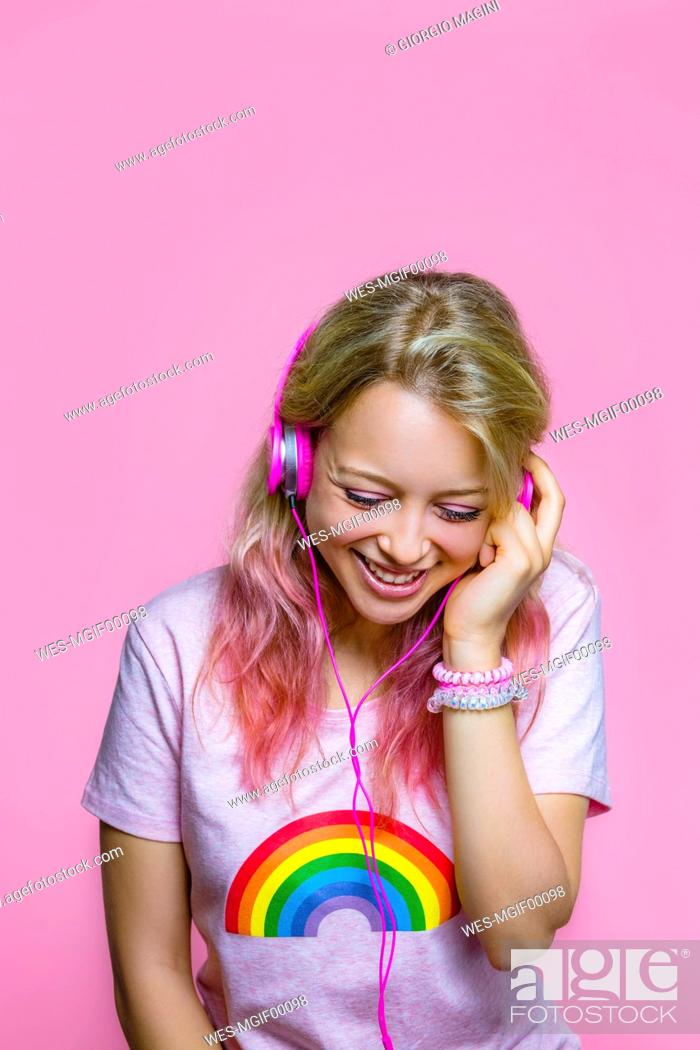 Stock Photo: Portrait of young woman listening to music with headphones in front of pink background.