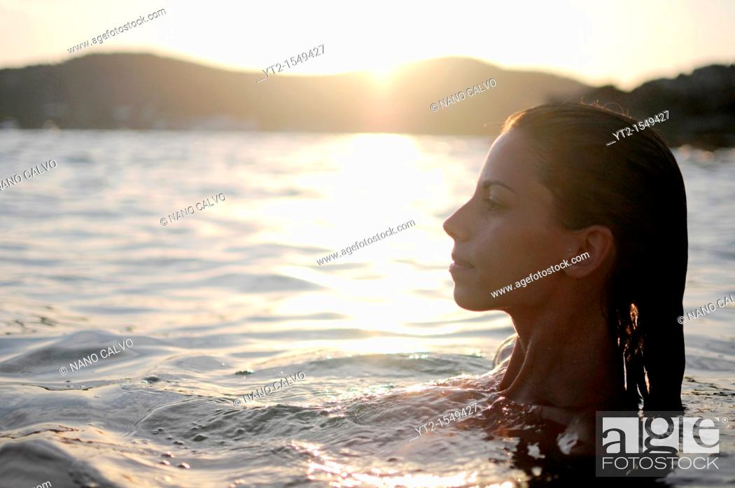 Stock Photo: Young attractive woman relaxing in Mediterranean Sea, at sunset.