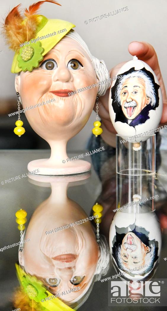 Stock Photo: 28 February 2021, Saxony, Leipzig: On a glass table by the collector and Easter egg artist Kerstin Dischereit, a goose egg with a portrait of Albert Einstein.