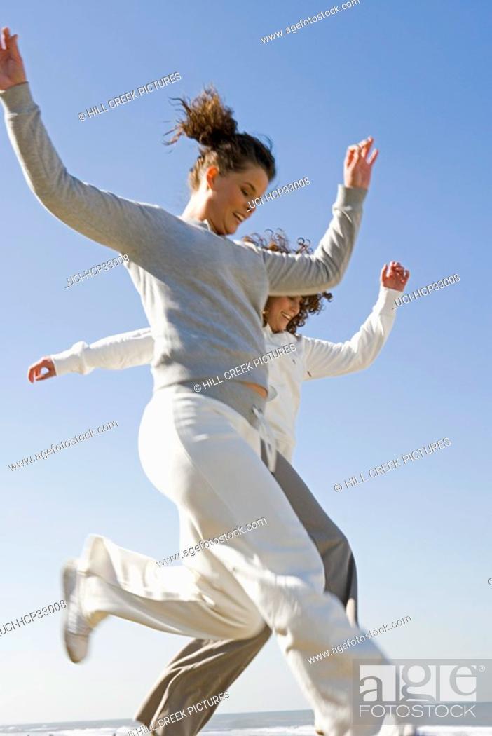 Photo de stock: Women jumping at beach.