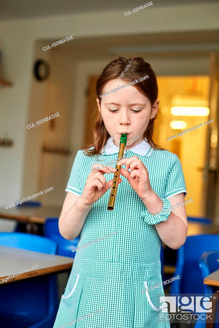 Photo de stock: Schoolgirl playing recorder in classroom at primary school.