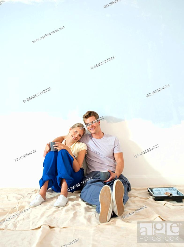 Stock Photo: Young couple taking a break from decorating.