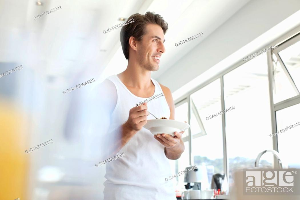 Stock Photo: Smiling man eating cereal in kitchen.