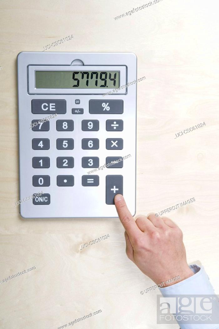 Stock Photo: Businessman touching calculator button.