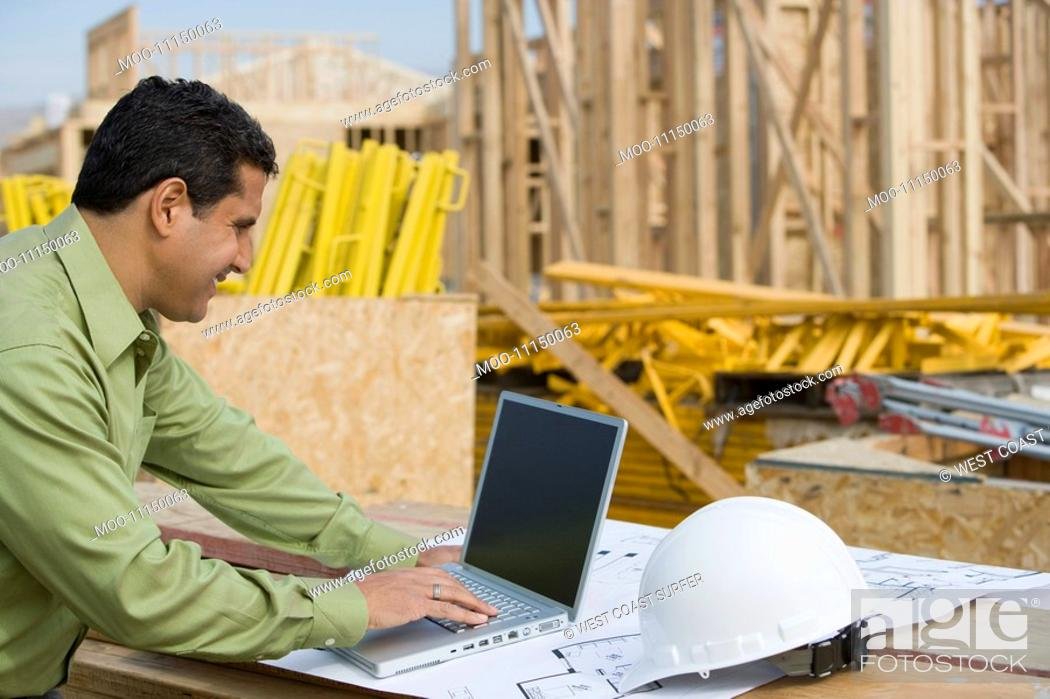 Stock Photo: Construction worker using laptop.