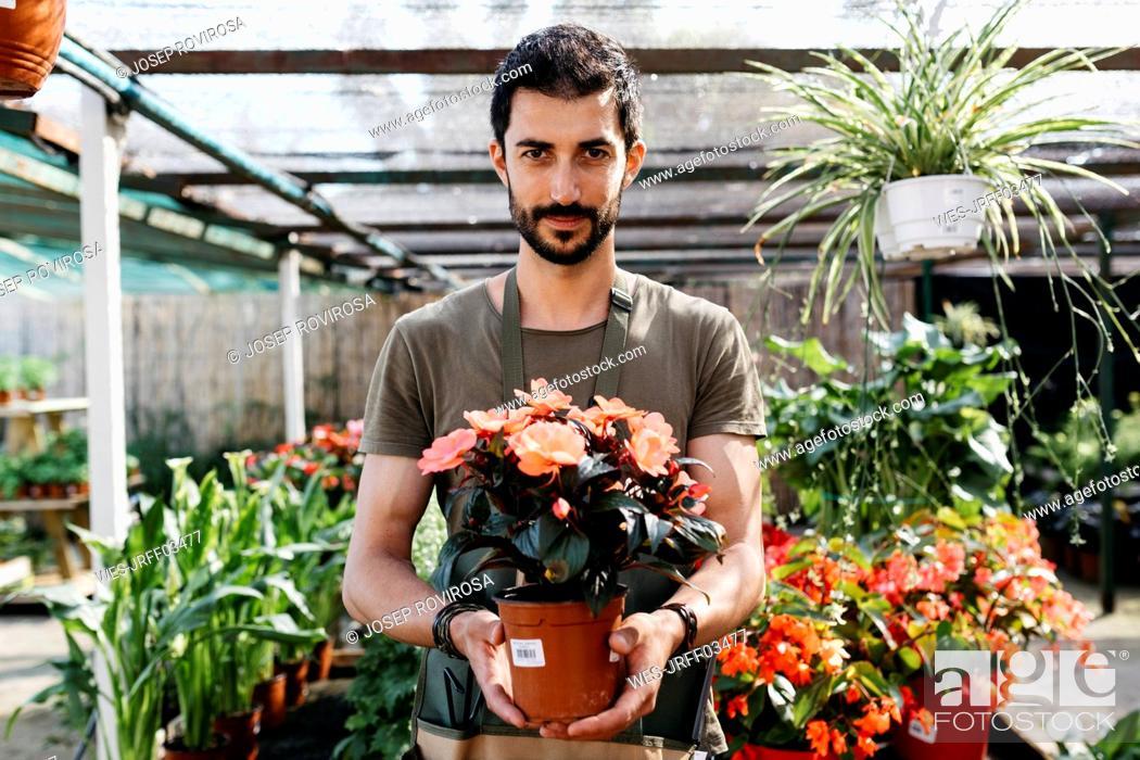 Imagen: Portrait of a gardener in a garden center holding flower.