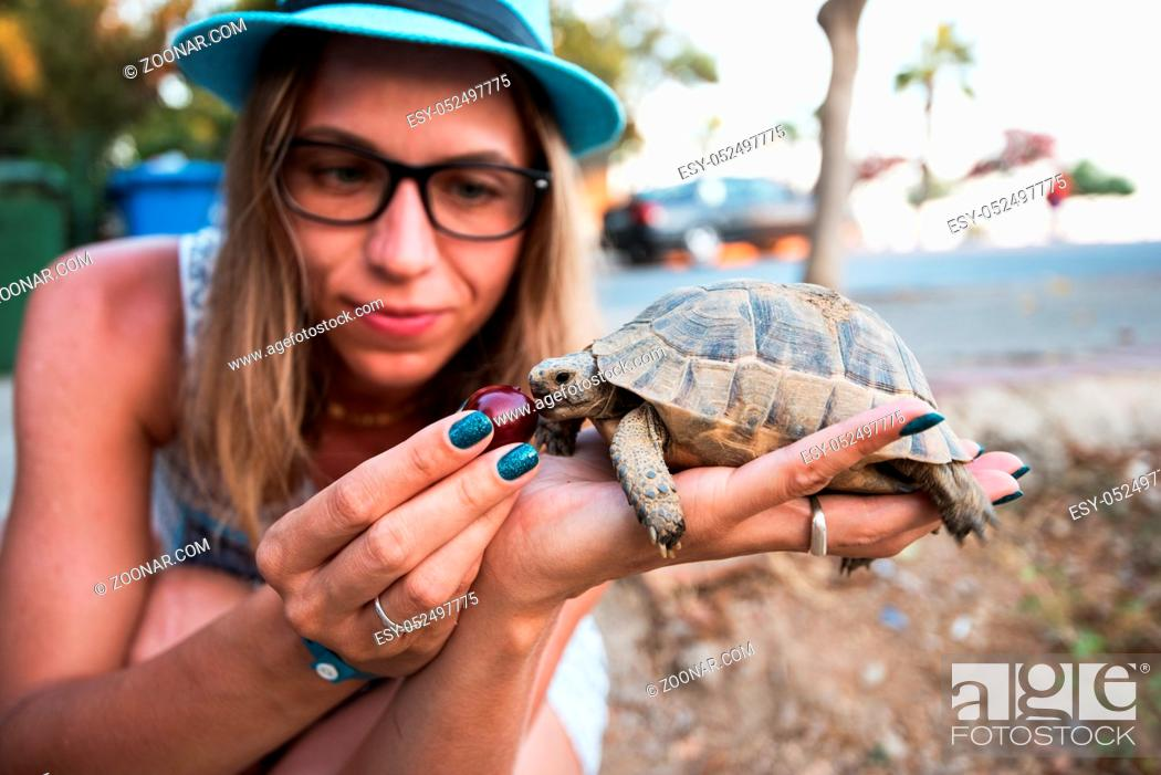 Stock Photo: Happy young woman feeding turtle with cherry.