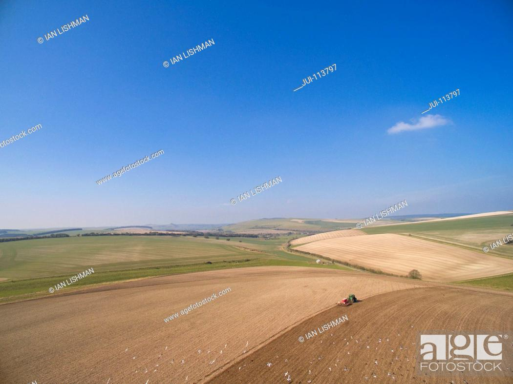 Stock Photo: Aerial View Of Tractor Pulling Drill Sowing Seed In Field.