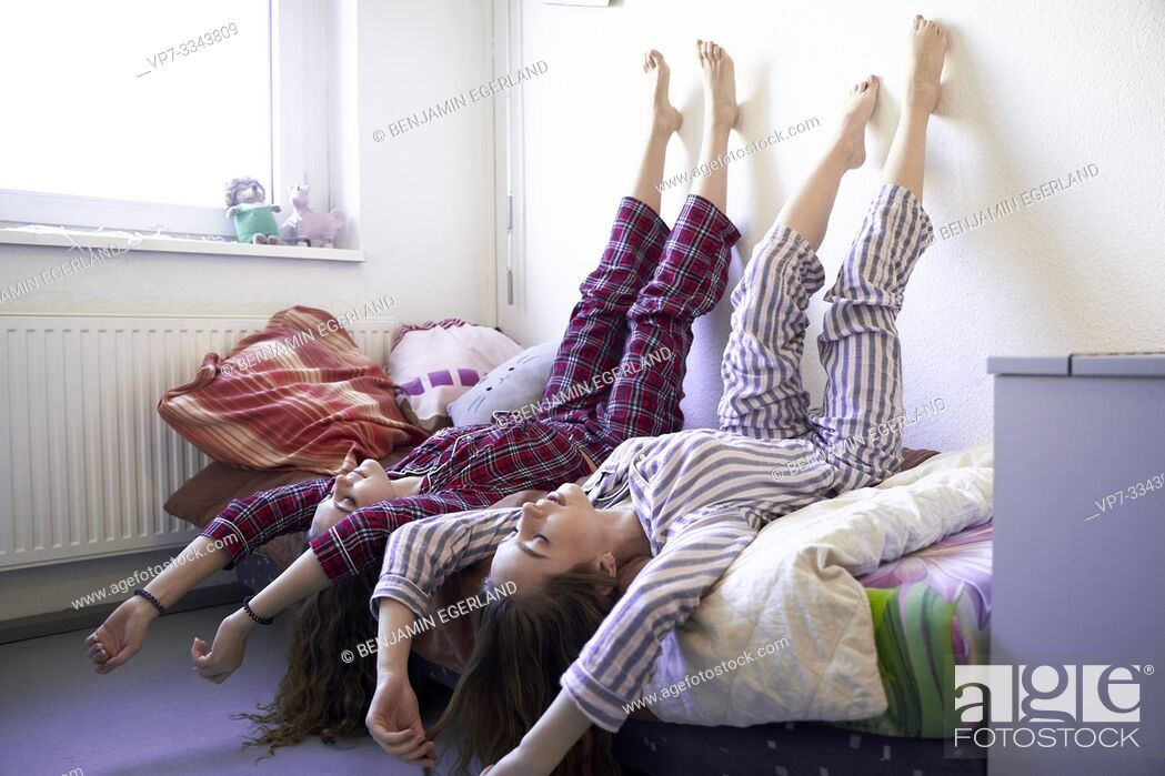 Stock Photo: two young women laying upside down in bed together, wearing pyjamas.