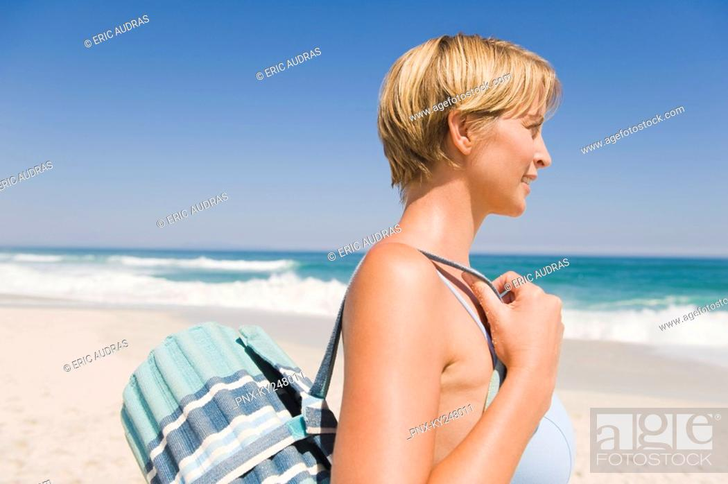 Stock Photo: Woman carrying a mat on the beach.