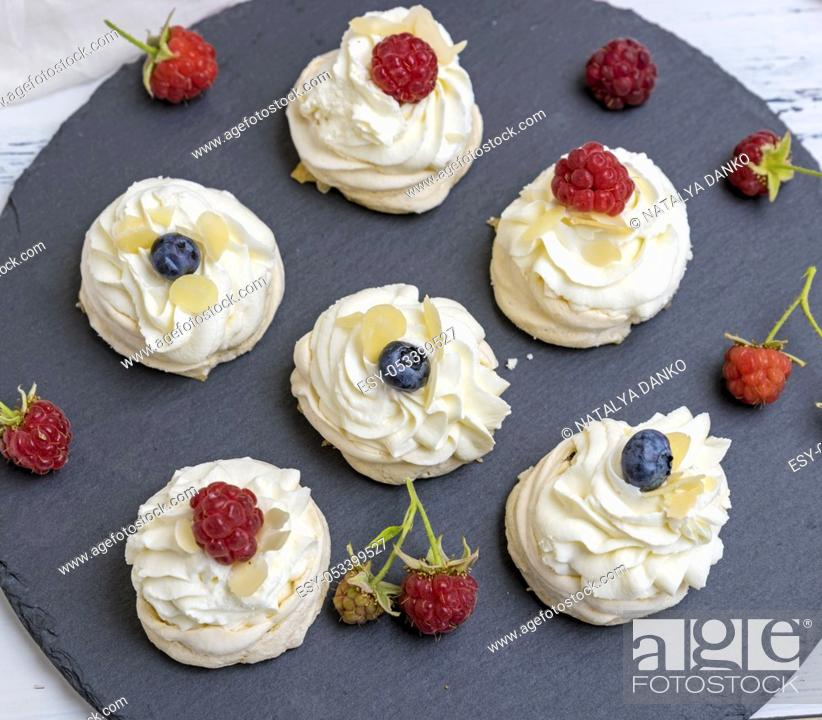 Stock Photo: round meringues with whipped cream on a black graphite board, top view.
