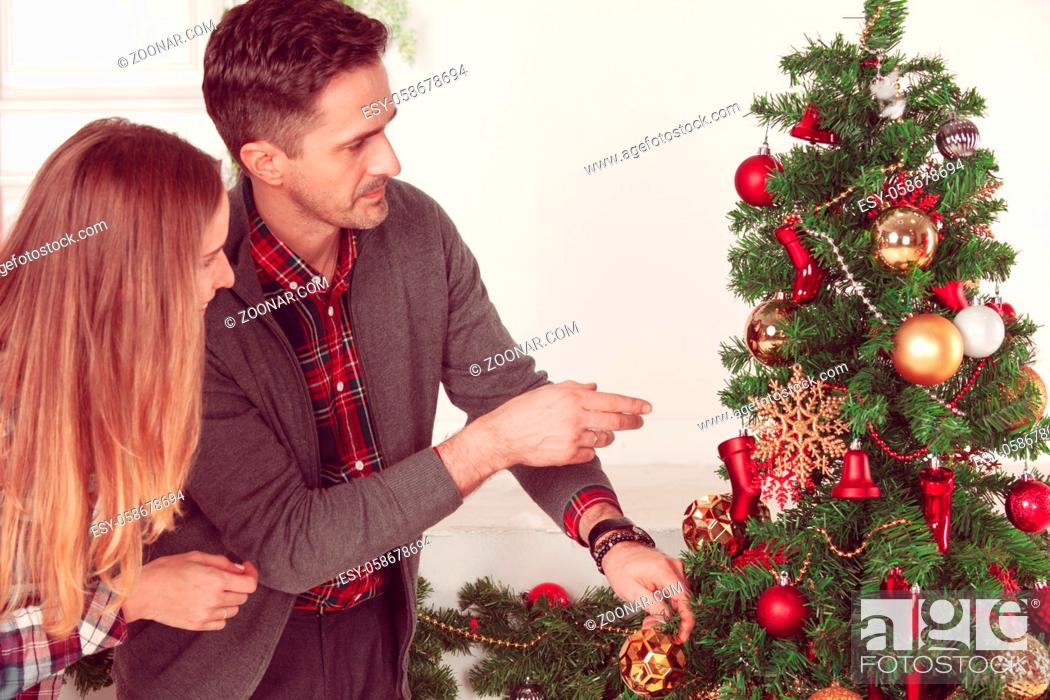 Stock Photo: Happy Couple Decorating Christmas Tree in their Home. Smiling Man and Woman together Celebrating Christmas or New Year. Christmas Tree Decoration.