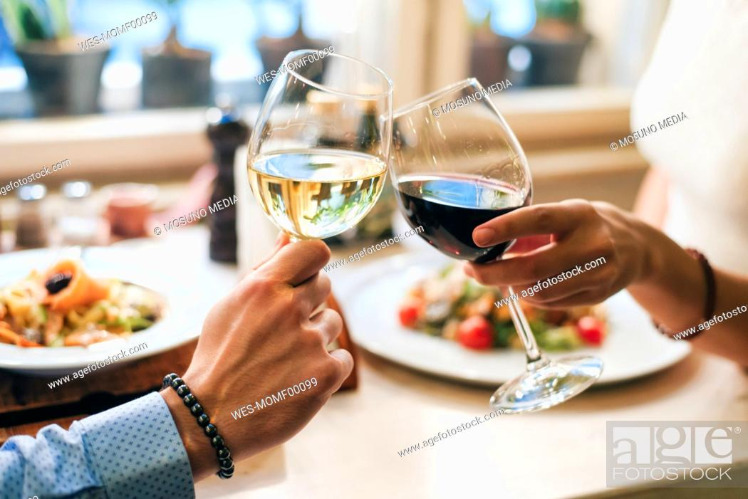Stock Photo: Couple toasting with wine, close-up.