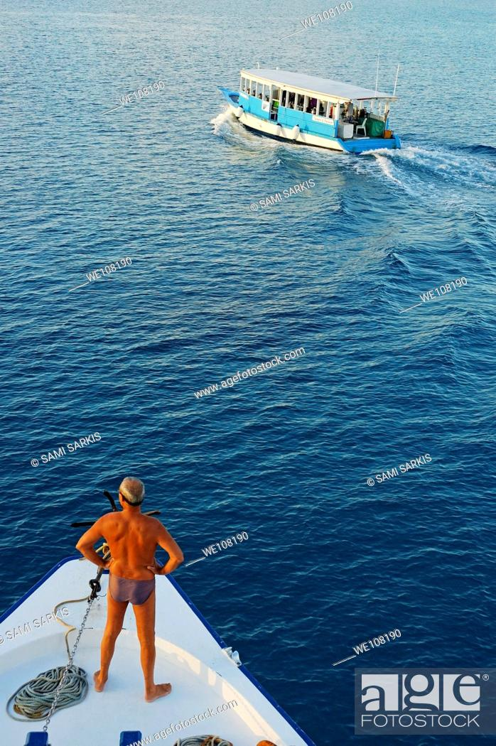 Stock Photo: Man standing on a ship's bow looking out to sea at a Dhoni boat, Maldives.
