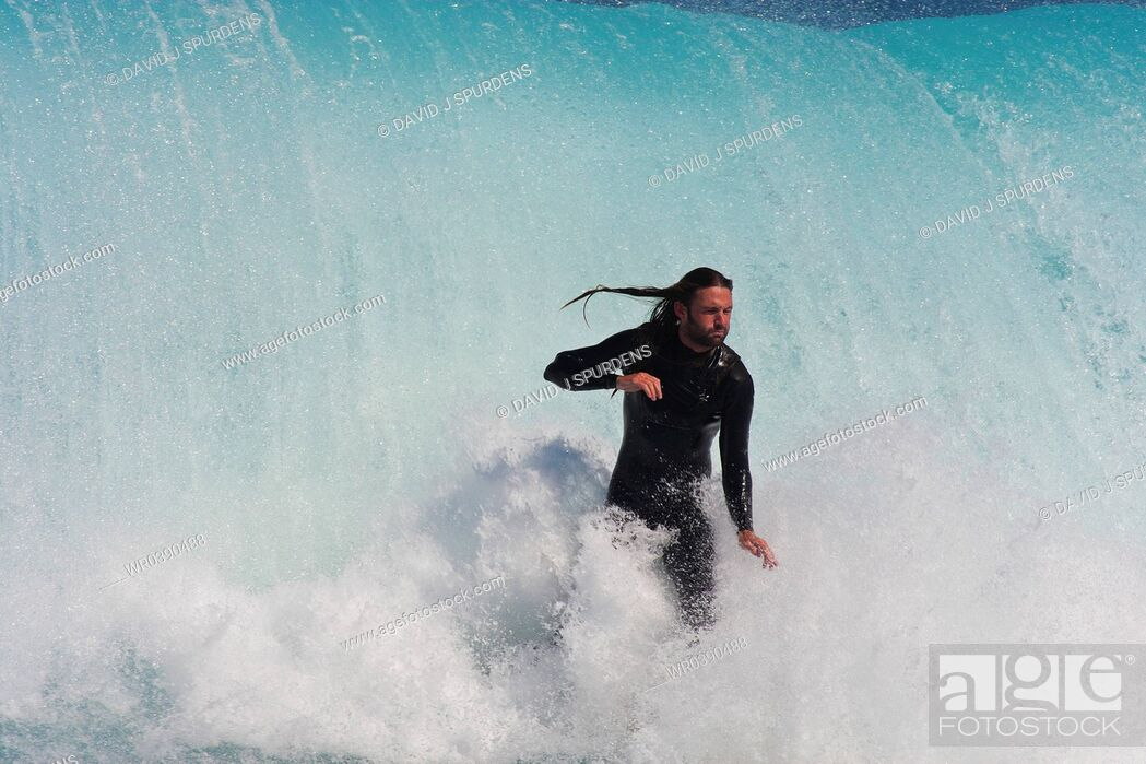 Stock Photo: This surfer takes a deep breath as he is about to be taken out by the massive wave behind him.